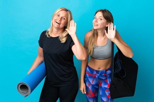 Moeder en dochter die yoga doen die op blauwe muur wordt geïsoleerd die naar iets luisteren door hand op het oor te leggen