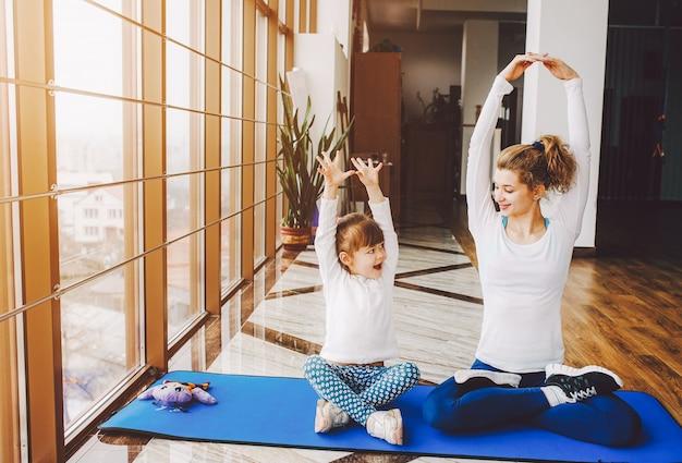 Moeder en dochter die yoga doen