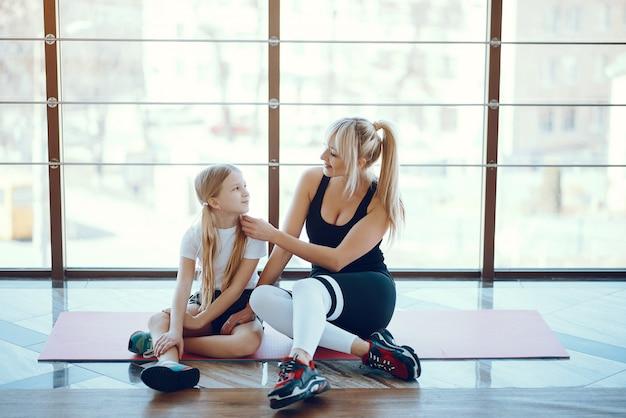 Moeder en dochter die yoga in een yogastudio doen