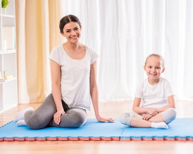 Moeder en dochter die yogaoefeningen op tapijt thuis doen.