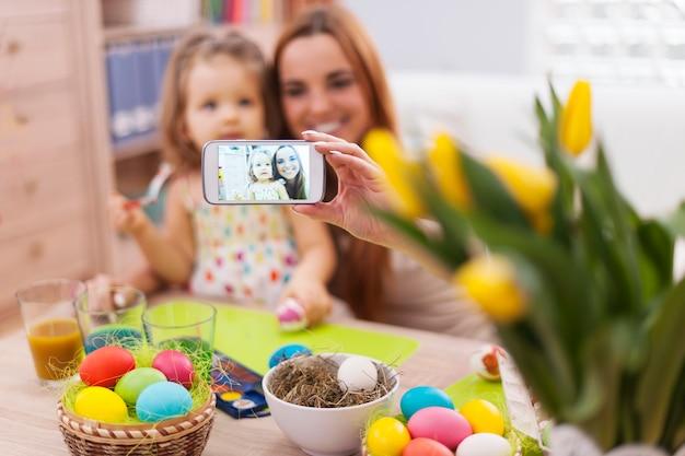 Moeder en dochter die zelfportret nemen terwijl pasen-tijd