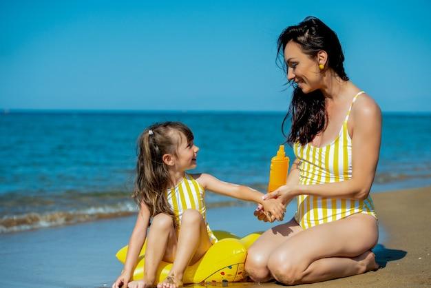 Moeder en dochter die zonnebrandcrème aanbrengen op lichaamsspf.