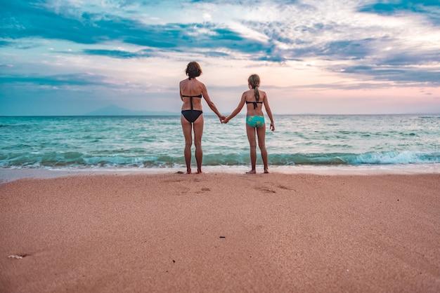 Moeder en dochter die zonsondergang strand bekijken