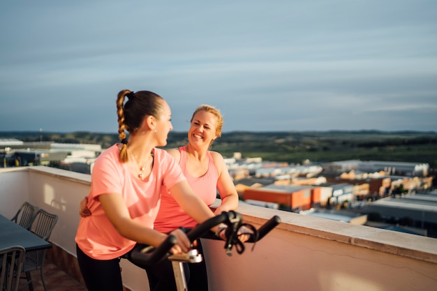 Moeder en dochter doen fietsoefeningen op terras van huis