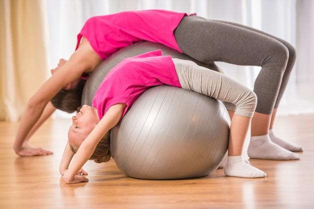 Moeder en dochter doen fysieke oefeningen op fitness bal