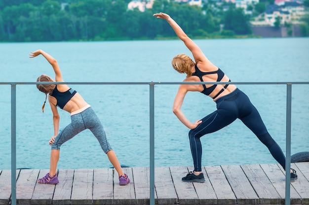 Moeder en dochter doen gymnastiekoefeningen op het gras bij de pijler van de rivier