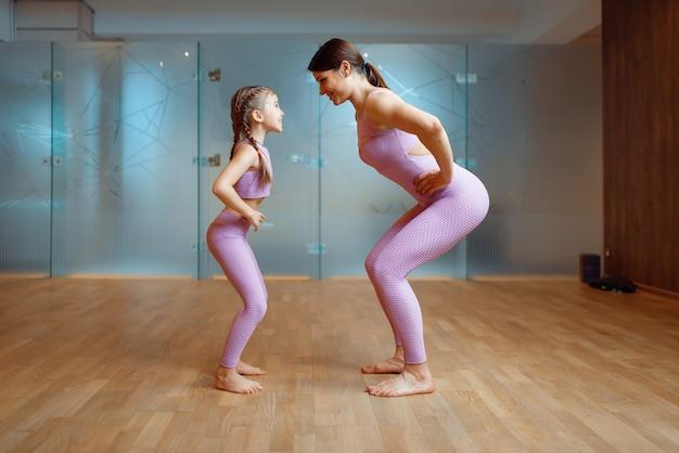 Moeder en dochter doen oefeningen in de sportschool, fitnesstraining. moeder en klein meisje in sportkleding, gezamenlijke training in sportclub