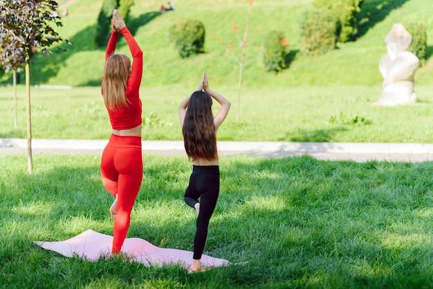 Moeder en dochter doen overdag yoga-oefeningen op gras in het park