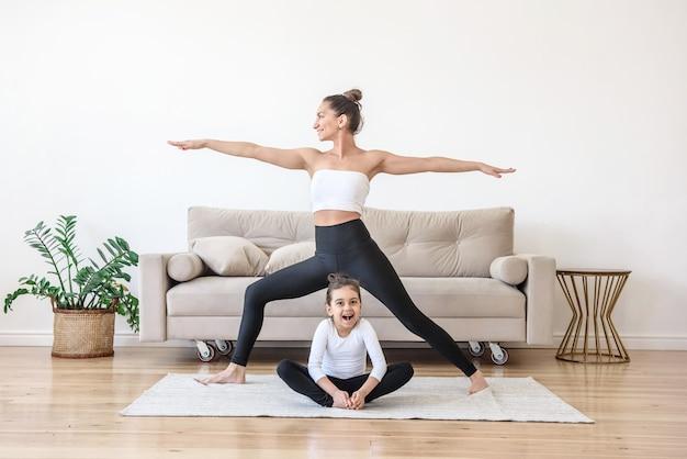 Moeder en dochter doen thuis 's ochtends samen yoga
