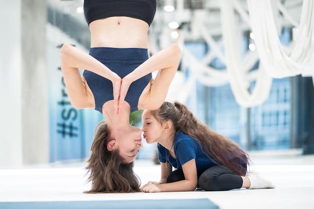 Moeder en dochter doen yoga. mam hangt ondersteboven