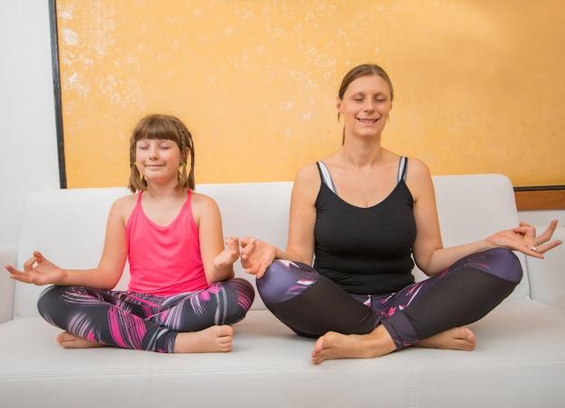 Moeder en dochter doen yoga-oefening, zitten thuis op de bank