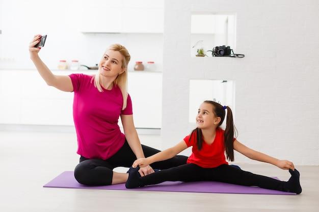 Moeder en dochter doen yoga-oefeningen op mat thuis.