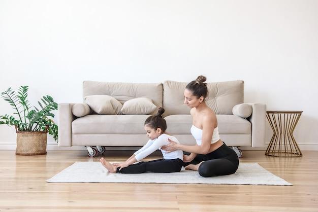 Moeder en dochter doen yoga thuis samen uitrekkende gymnastiek