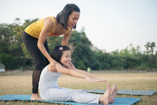 Moeder en dochter doen yoga. vrouw en kind training in het park. buitensport. gezonde sport levensstijl, zittend in paschimottanasana oefening, zittende voorwaartse buiging pose.