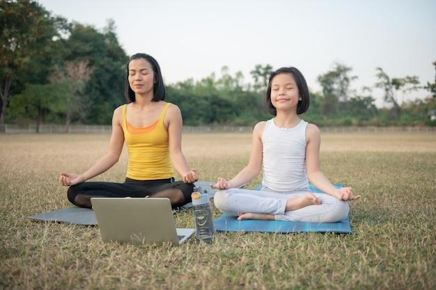 Moeder en dochter doen yoga. vrouw en kind training in het park. buitensport. gezonde sportlevensstijl, kijken naar yoga-oefeningen online video-tutorial en meditatieoefeningen tijdens het sporten.