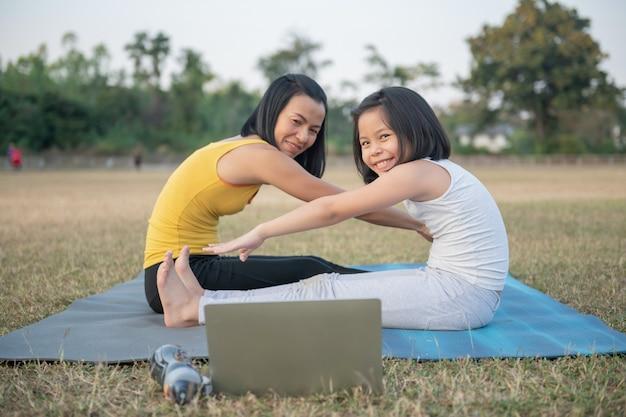 Moeder en dochter doen yoga. vrouw en kind training in het park. buitensport. gezonde sportlevensstijl, kijken naar yoga-oefeningen online video-tutorial en zittende voorwaartse buiging.
