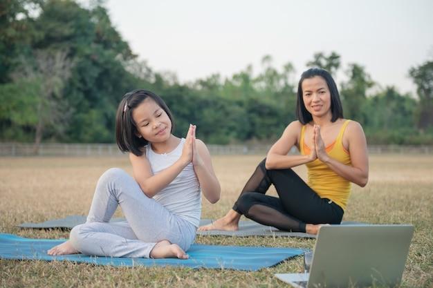Moeder en dochter doen yoga. vrouw en kind training in park. buitensport. gezonde sportlevensstijl, kijken naar yoga-oefeningen online video-tutorial en stretchen in ardha matsyendrasana pose