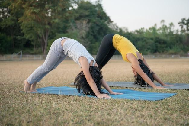 Moeder en dochter doen yoga. vrouw en kind training in park. buitensporten.gezonde sportlevensstijl, kijken naar yoga-oefeningen online video-tutorial en strekken in neerwaarts gerichte hondenoefening