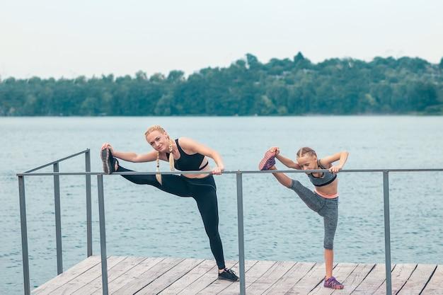 Moeder en dochter doet fitness oefeningen op een pier