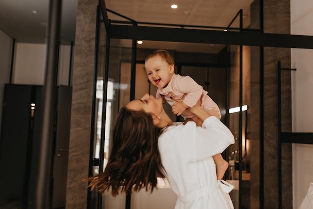 Moeder en dochter dollen in hun stijlvolle appartementen. portret van langharige dame met lachend kind.