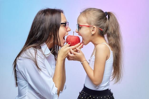 Moeder en dochter dragen een bril en bijten in een big red apple.