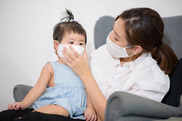 Moeder en dochter dragen thuis beschermend masker