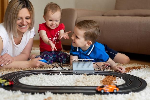 Moeder en dochter en zoon spelen racen op het tapijt.