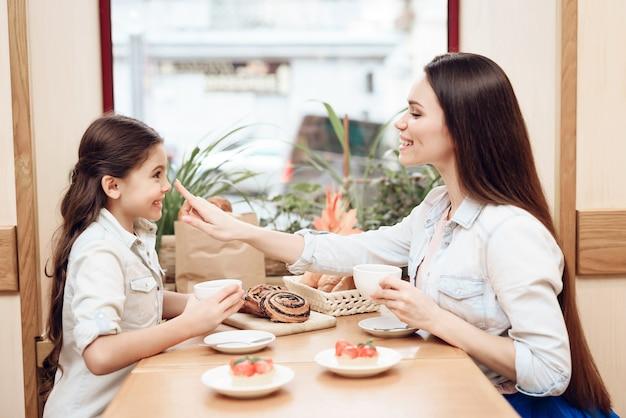 Moeder en dochter eten in koffie.