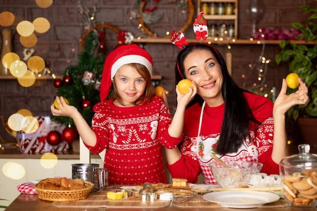 Moeder en dochter eten mandarijnen in een donkere keuken met een kerstboom voor nieuwjaar of kerstmis, glimlachen, dollen en hebben samen plezier in afwachting van de vakantie in een kerstmanhoed
