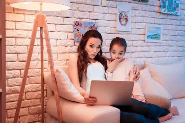 Moeder en dochter films kijken op laptop.