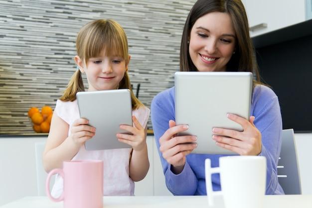 Moeder en dochter gebruiken een digitale tablet in de keuken