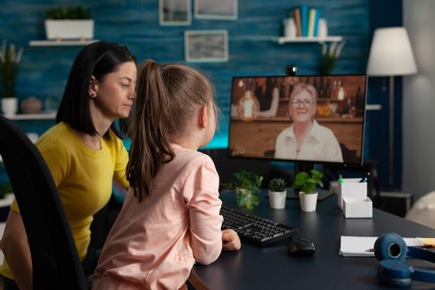 Moeder en dochter gebruiken videoconferentietechnologie voor moderne communicatie. volwassene en kind praten met oma oude dame op online internetverbinding terwijl ze thuis zitten