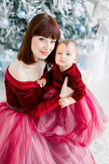 Moeder en dochter, gekleed in rode jurken, zittend op de achtergrond van de kerstboom