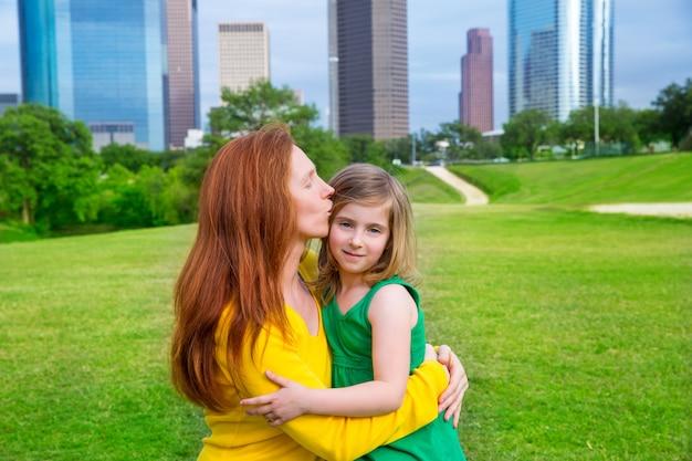Moeder en dochter gelukkige knuffelkus in park bij stadshorizon