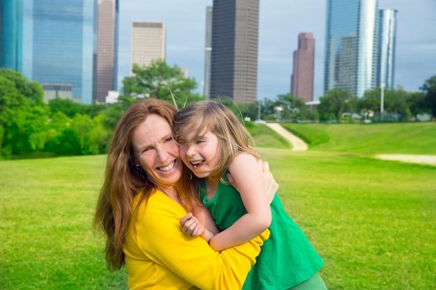 Moeder en dochter gelukkige omhelzing die in park bij stadshorizon lachen