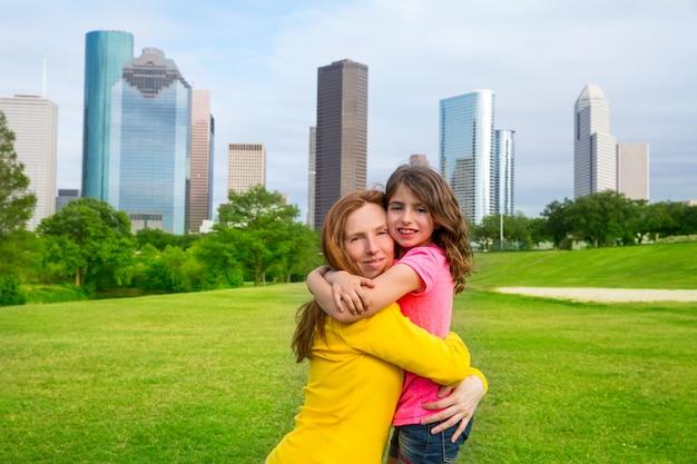 Moeder en dochter gelukkige omhelzing in park bij stadshorizon