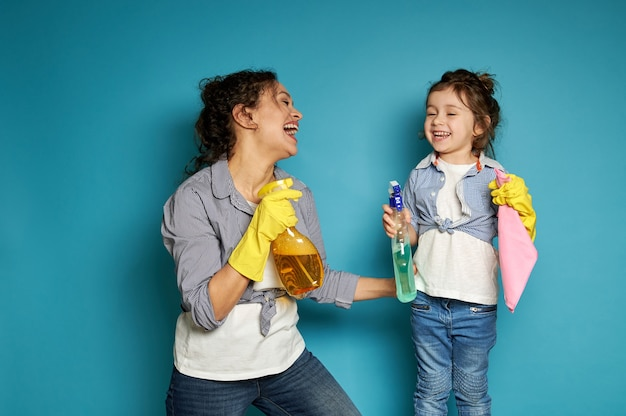Moeder en dochter genieten van tijd samen tijdens het thuiswerk, staand tegen blauw en gelukkig lachend