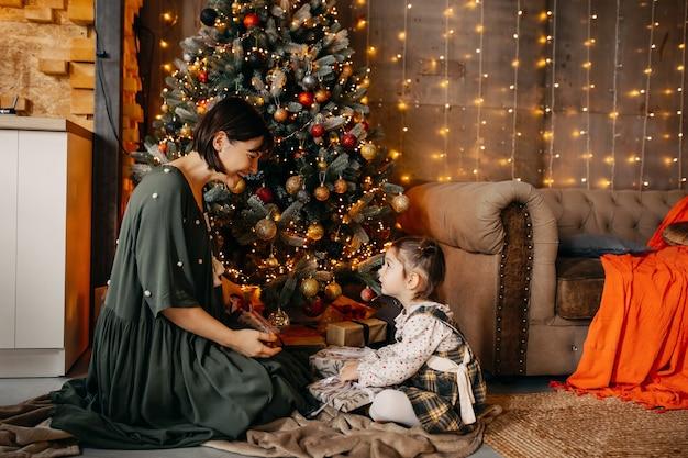 Moeder en dochter geven elkaar geschenken, zittend naast een kerstboom