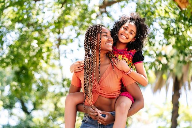 Moeder en dochter glimlachen en genieten van een dag samen in het park