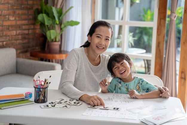 Moeder en dochter glimlachen terwijl samen leren