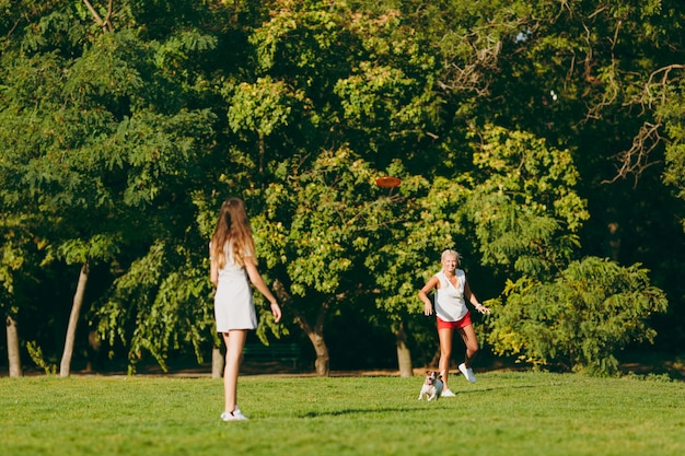Moeder en dochter gooien oranje vliegende schijf naar kleine grappige hond, die hem op groen gras vangt. kleine jack russel terrier huisdier buiten spelen in het park. hond en vrouwen. familie rustend op open lucht