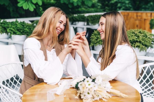 Moeder en dochter hand in hand en lachend in het café