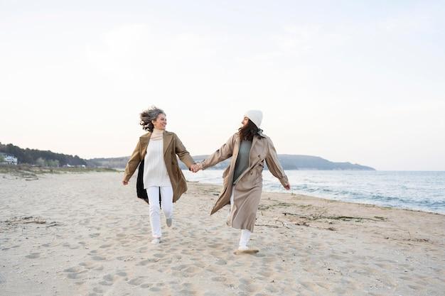 Moeder en dochter hand in hand terwijl ze samen op het strand zijn