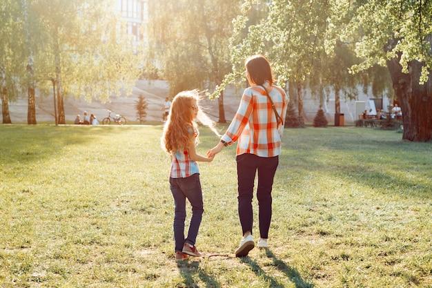 Moeder en dochter hand in hand wandelen in het park, gouden uur
