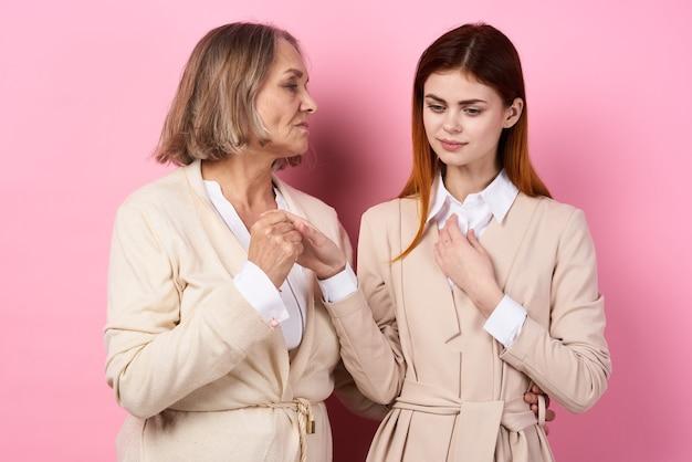 Moeder en dochter hand in hand zorgzame familie houden samen van roze achtergrond