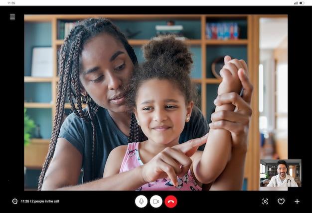 Moeder en dochter hebben een videogesprek met de dokter voor een consult terwijl ze thuis blijven. nieuwe normale levensstijl. gezondheidszorg en geneeskundeconcept.