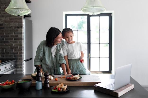 Moeder en dochter hebben een videogesprek vanuit hun keuken