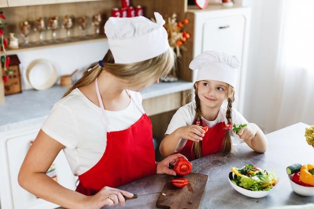 Moeder en dochter hebben plezier in de keuken en koken verschillende groenten voor een diner