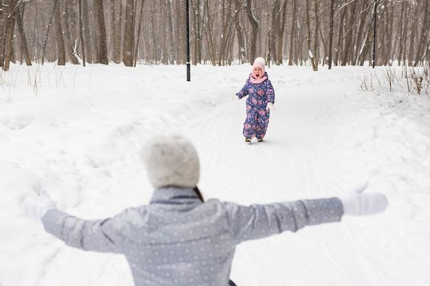 Moeder en dochter hebben plezier in het winterpark.