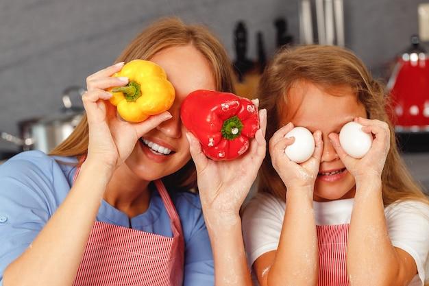 Moeder en dochter hebben plezier met eten tijdens het koken in de keuken